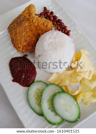 Famous Malaysian food known as Nasi Lemak on white plate.