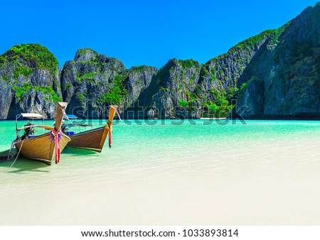 Famous Maya Bay beach at Ko Phi Phi Leh Island with two traditional longtail taxi boats mooring and steep limestone hills in background. Main Thailand tourist attraction, Krabi Province, Andaman Sea