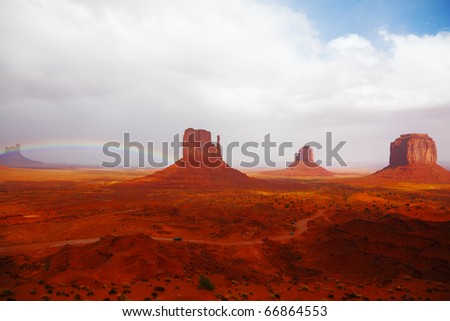 Famous mittens of red sandstone in a fog after the storm and a rainbow in the sky