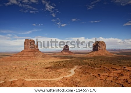 Famous Monument Valley, Arizona, USA. Monument Valley Navajo Tribal Park Panorama - Summer Cloudy Blue Sky. Colorado Plateau Characterized by a Cluster of Vast Sandstone Buttes. Valley Panorama