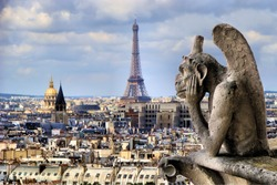 Famous Notre Dame gargoyle overlooking the Paris cityscape with Eiffel Tower