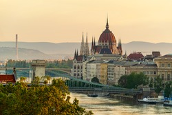 Famous part of Budapest with Hungarian parliament buildin's towers and Chain bridge over the danube river. Beautiful golden colors in sunrise time. Colorful clean photo