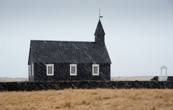 Famous picturesque black church of Budir at Snaefellsnes peninsula region in Iceland during a heavy snowy weather