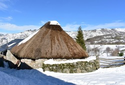 Famous Piornedo mountain village after a snowfall with ancient round Palloza stone houses with thatched roofs. Ancares, Lugo, Galicia, Spain.
