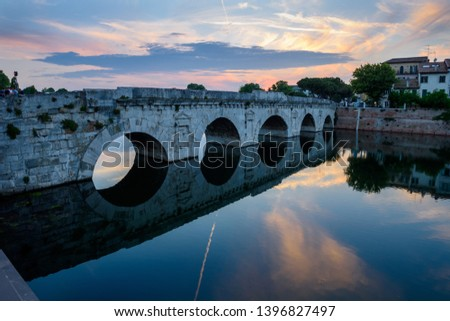 Famous place in Rimini, Italy. Beautiful sunset over the Tiberius Bridge, with reflection in the river. #1396827497