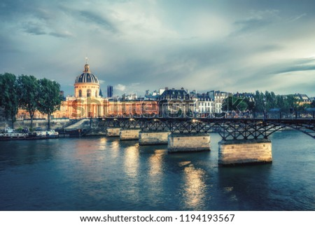 Famous Pont des Arts in Paris, France at night. Spectacular cityscape with dramatic sunset sky. #1194193567