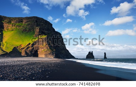 Famous Reynisdrangar rock formations at black Reynisfjara Beach. Coast of the Atlantic ocean near Vik, southern Iceland.