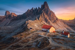 Famous Rifugio Locatelli alpine hut and cute small chapel with spectacular Monte Paterno peaks in background at sunset, Dolomites, Italy, Europe