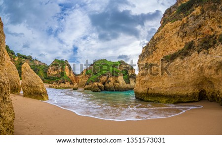 Famous rock formation in a bay on the beach of Tres Irmaos in Alvor, Portimão, Algarve, Portugal, Europe. Praia dos Tres Irmaos. View between two rocks.