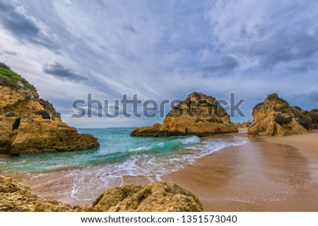 Famous rock formation in a bay on the beach of Tres Irmaos in Alvor, Portimão, Algarve, Portugal, Europe. Praia dos Tres Irmaos.The sun shines through the clouds, the waves roll on the sand.