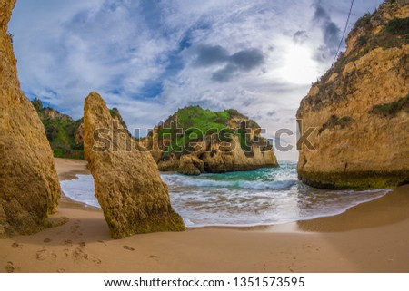 Famous rock formation in a bay on the beach of Tres Irmaos in Alvor, Portimão, Algarve, Portugal, Europe. Praia dos Tres Irmaos.The sun shines through the clouds, the waves roll on the sand