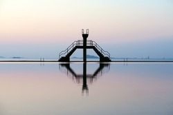 Famous Saint-Malo outdoor swimming pool with jumping platform and its symmetrical reflection in hight tide ocean water, Brittany, France