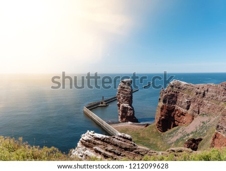 famous sea stack Lange Anna on island of Heligoland against blue sea and sky on sunny day