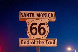 Famous sign of the end of the route 66 trail. Pacific park of Santa Monica pier. Colorful wheel and neons lights. Historic place in Los Angeles.