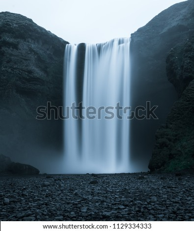 Famous Skogafoss Waterfall in Iceland from the front with silky looking water falling off the hill in a dark look with black stones in the foreground and no people in front during night