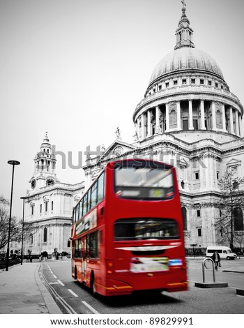 Famous St. Paul's Cathedral with iconic red bus in London speeding past