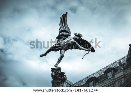 Famous statue of Eros, Amor, Cupid at Piccadilly Circus in London, UK, on blue clear sky and dramatic background  #1417681274
