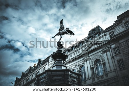Famous statue of Eros, Amor, Cupid at Piccadilly Circus in London, UK, on blue clear sky and dramatic background  #1417681280