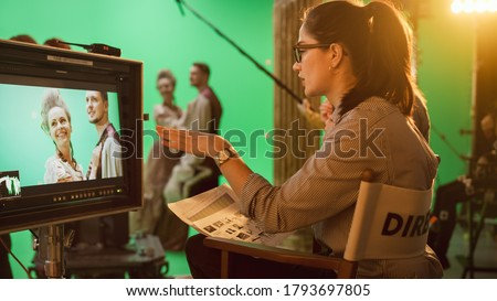 Famous Talented Female Director in Chair Looks at Display Following Shootings of a New Blockbuster. Green Screen Scene in Historical Drama. Film Studio Set Professional Crew Doing High Budget Movie