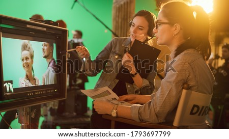 Famous Talented Female Director in Chair Looks at Display talks with Assistant, Shooting Blockbuster. Green Screen Scene in Historical Drama. Film Studio Set Professional Crew Doing High Budget Movie