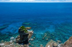 Famous Tategami Iwa stone surrounded by lush transparent turquoise sea, coral reefs and so many rocks under the water seeen from a high cliff. Yonaguni Island.