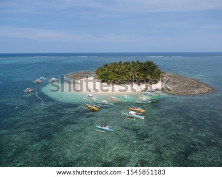 Famous tourism island in Siargao, Surigao del Norte, Philippines, South East Asia; Guyam Island, Palm tree covered sandy beach island in the middle of the ocan with clear blue water and coral reef. #1545851183
