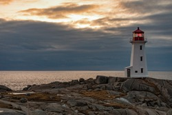 Famous tourist attraction Peggy's Cove Lighthouse on granite rock cliffs overlooking calm Atlantic Ocean, Nova Scotia, NS, Canada