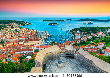 Famous touristic and travel destination. View from the Tvrdava Fortica (Spanjola) fortress at sunset. Green islands, blue lagoons and fantastic harbor, Hvar, Hvar island, Dalmatia, Croatia, Europe