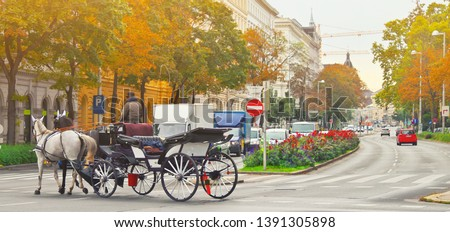 Famous traditional horse drawn fiaker carrige in the old historic center street of Vienna, Austria. Everyday life of evropean culture capital near Hofburg palace. Travel vacation in Vienna, Austria