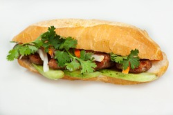 Famous Vietnamese food is banh mi thit, popular street food from bread stuffed with raw material: grilled pork and fresh herbs as scallions, coriander, carrot, cucumber, chilli. On White