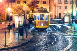 Famous vintage yellow 28 tram of of Alfama, in the oldest district of the Old Town, at night, Lisbon, Portugal.