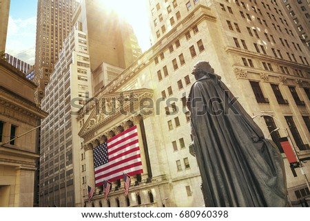 Famous Wall street and the building in New York, New York Stock Exchange with patriot flag #680960398