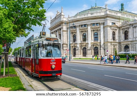Famous Wiener Ringstrasse with historic Burgtheater (Imperial Court Theatre) and traditional red electric tram