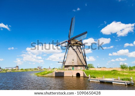 Famous windmills in Kinderdijk village in Holland. Colorful spring landscape during summer sunny day in Netherlands, Europe. UNESCO World Heritage and famous tourist site.