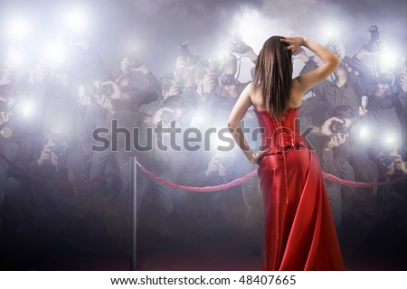 famous woman posing in front of paparazzi - stock photo