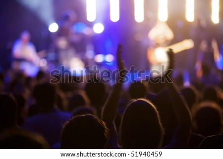 Fan cheering at live concert, some motion blur at arms, soft focus. #51940459