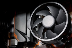 Fan cooling system of computer's CPU which is installed on the motherboard circuit. Close-up and selective focus on some part of the fan's fin.