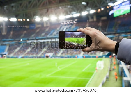 Fan hand with smartphone photographing football game