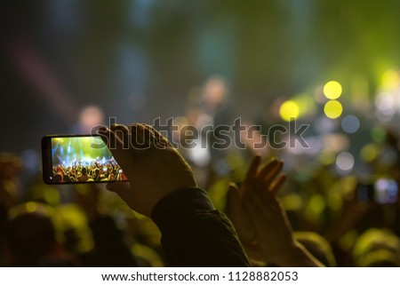Fan holding smartphone and recording or taking picture during a  concert