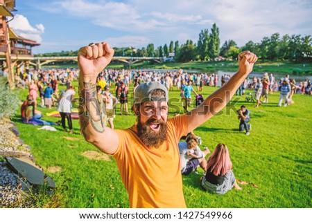 Fan zone. Entertainment concept. Visit summer festival. Summer fest. Hipster in cap happy celebrate event fest or festival. Man bearded hipster in front of crowd. Open air concert. Music festival.