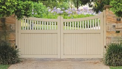 Fancey Automatic wooden entrance gate across a driveway