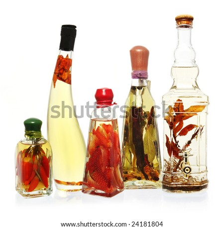 Fancy bottles of infused oils and vinegars.  Infusions include chili peppers, garlic, and strawberries.  Glass bottles reflected on white surface.