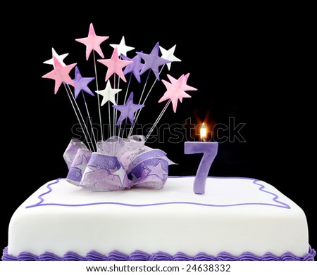 Fancy cake with number 7 candle.  Decorated with ribbon and star-shapes, in pastel tones on black background.