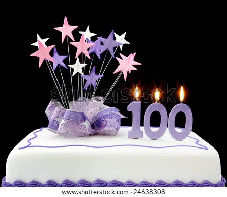 Fancy cake with number 100 candles.  Decorated with ribbons and star-shapes in pastel tones against black background. - stock photo