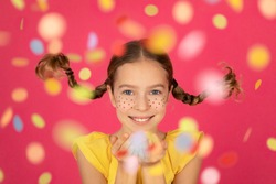 Fancy child with pigtails blowing confetti. Portrait of funny girl against pink background. Christmas holiday concept