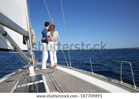 Fancy couple enjoying sailing on a beautiful sailboat