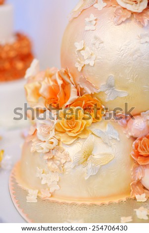 Fancy delicious white and yellow wedding cake decorated with flowers and butterflies