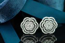 Fancy diamonds earrings with blue ribbon on black isolated