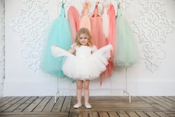 fancy dresses for girls. baby in a white, lush, elegant dress near the hanger with festive clothes. fashion for children. shop.
