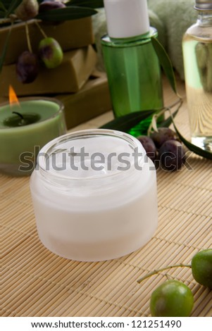 Fancy face cream  with olive soap bars, olive oil, and scented candles for spa treatment